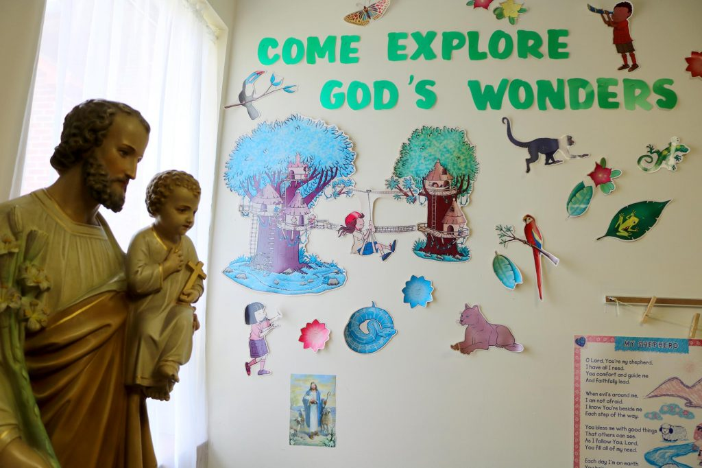 """Decorations on a wall that read, """"Come explore God's Wonders,"""" along with a statue of St. Joseph holding the Christ Child in a Sunday school classroom at Holy Trinity Catholic Church"""