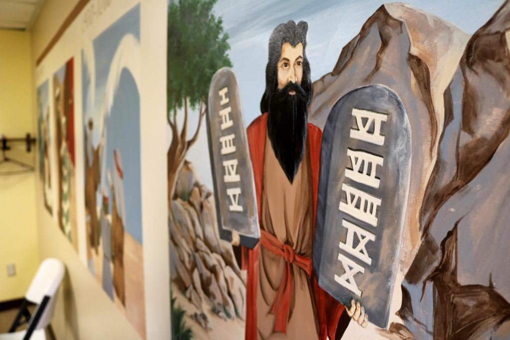 A mural Old Testament Bible stories including Moses holding two stone tablets with the ten commandments on them, in a Sunday school classroom at Holy Trinity Catholic Church