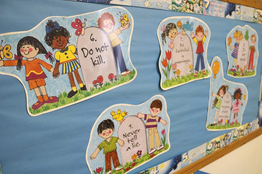 Cartoon pictures of children standing next to stone tablets, each with one of the ten commandments on it, in a Sunday school classroom at Holy Trinity Catholic Church