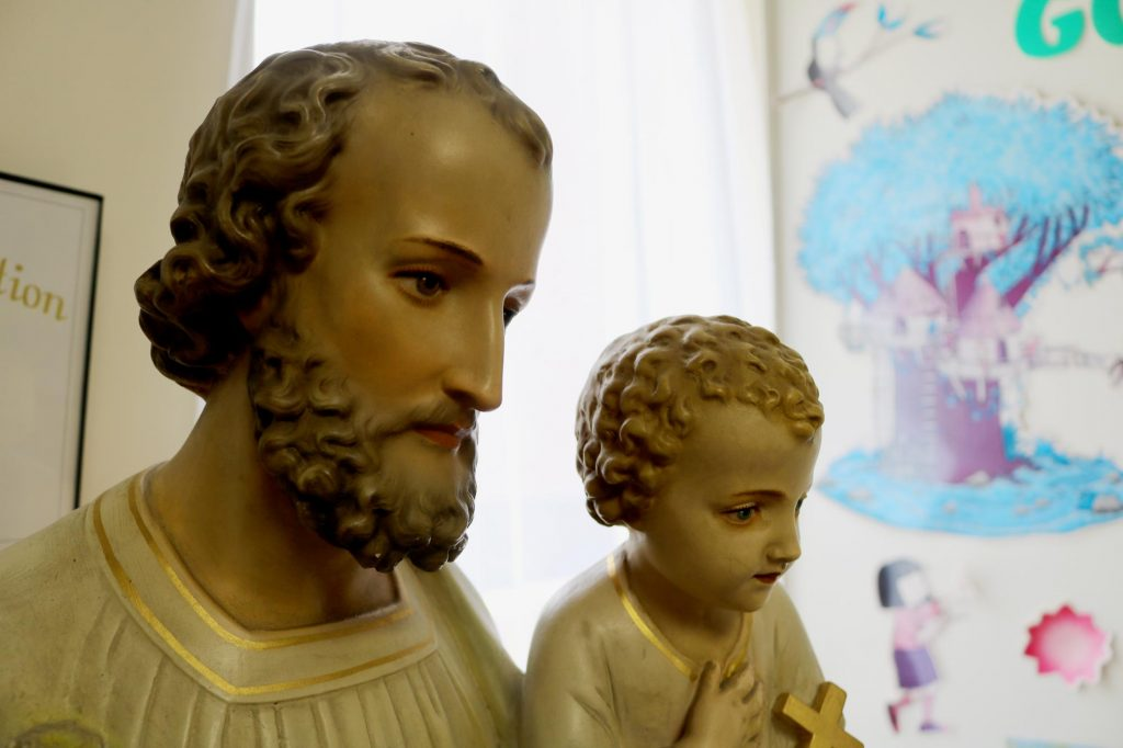 A statue of St. Joseph holding the Christ Child in a Sunday school classroom at Holy Trinity Catholic Church