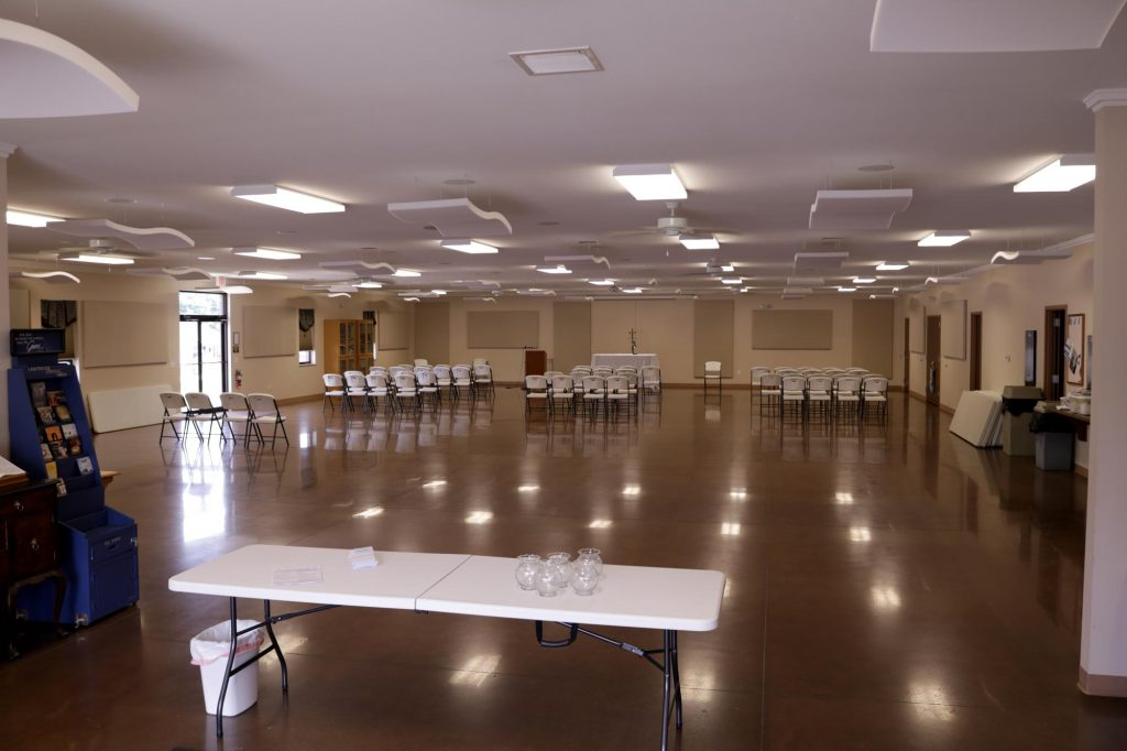 Parish hall interior with tables and chairs set up for a special event at Holy Trinity Catholic Church