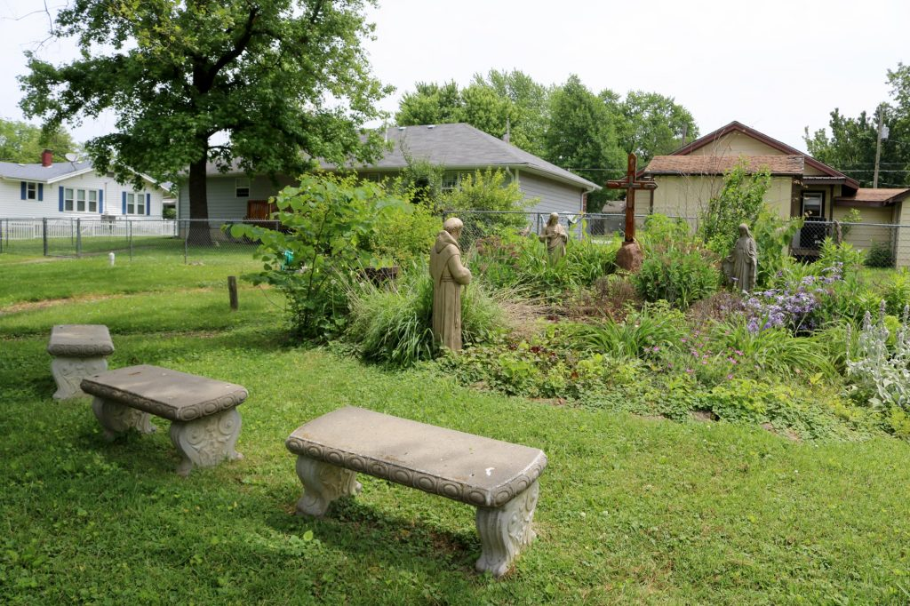 Prayer garden featuring a wooden cross, religious statues, a Rosary walking path, and concrete benches, among grass and flowers.