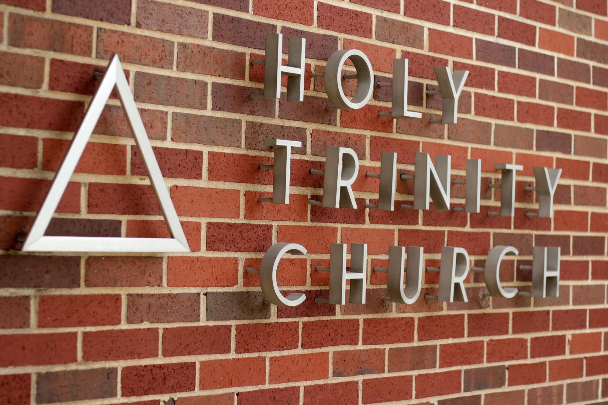 Sign on the building at Holy Trinity Catholic Church, with the name of the parish