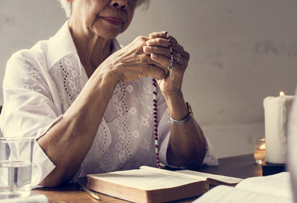 Woman praying while holding a Rosary and sitting with a Bible